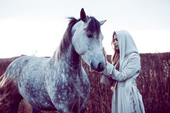 Girl in the hooded cloak with horse, effect of toning. Portrait of a beauty blondie with horse royalty free stock photography