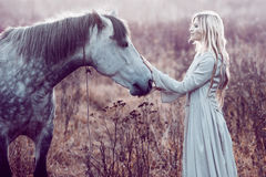 Girl in the hooded cloak with horse, effect of toning. Portrait of a beauty blondie with horse royalty free stock photos