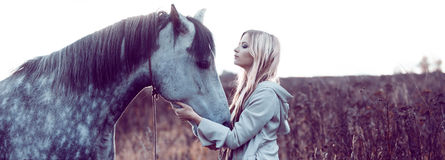 Girl in the hooded cloak with horse, effect of toning. Portrait of a beauty blondie with horse royalty free stock image