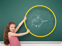 Girl with hoop draw helicopter and cloud on board Stock Image