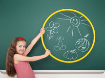 Girl with hoop draw sun and flower on board Stock Photos