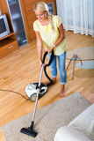 Girl hoovering in living room Stock Photos