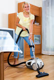 Girl hoovering in living room Royalty Free Stock Photography