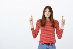 Girl hopes delivery guy will come in time. Portrait of worried impatient young woman in striped outfit, crossing fingers. And biting lip, looking aside at clock royalty free stock photos