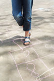 Girl hoping in hopscotch outdoors Royalty Free Stock Photo