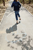 Girl hopping in hopscotch on urban alley Royalty Free Stock Photos