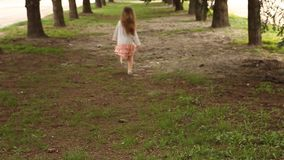 Girl hopping and runs away. From camera in straight arrows of pine trees in park stock footage