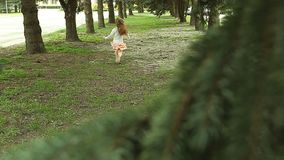 Girl hopping and runs away. From camera in straight arrows of pine trees in park stock video