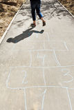 Girl hops in hopscotch on urban alley Stock Photo