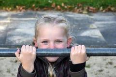 Girl at horizontal bar. Cute little girl  tries doing exercises at a horizontal bar Royalty Free Stock Photography