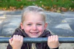 Girl at horizontal bar. Cute little girl  tries doing exercises at a horizontal bar Stock Photography