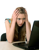 Girl with horror looks at the laptop screen Stock Images