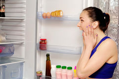 Girl in horror at the open refrigerator Stock Photos