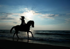 Girl on horse. The sun is setting, silhouette, empty horizon Stock Image
