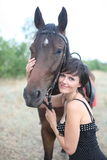 The girl and horse. The girl costs near a stable and irons a horse royalty free stock image