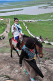 Girl on horse. A young tourist girl is riding a horse, which is conducted by a middle-aged Tibet woman,to climb mountains by Yellow River in Sichuan,China Stock Photo