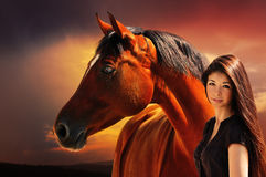 Girl and horse on the background of dramatic sky