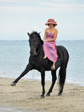 Girl and  horse on the beach Stock Image