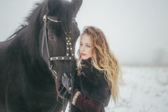 A girl with a horse in a field in winter Royalty Free Stock Photos