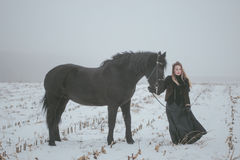 A girl with a horse in a field in winter.  Royalty Free Stock Image