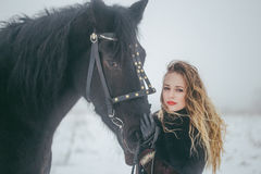A girl with a horse in a field in winter Royalty Free Stock Images