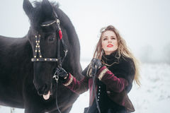 A girl with a horse in a field in winter Stock Photos
