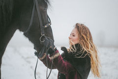 A girl with a horse in a field in winter Royalty Free Stock Photo