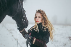 A girl with a horse in a field in winter Stock Photo