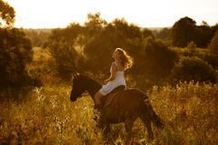 Girl on a horse of high grass Stock Image