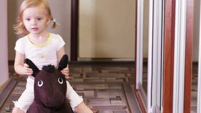 Girl on horse. Home girl rides on toy horse stock footage