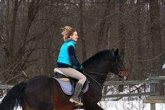 A girl on a horse  jumps  gallops. A girl trains riding a horse in a small paddock. A cloudy winter day.  Stock Photos