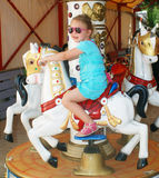 Girl and horse. A little girl is driving on a carousel Stock Image