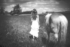 Girl with horse on meadow Stock Photo