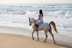 Girl horse ride beach. Girl in white dress enjoying horse ride on the beach Royalty Free Stock Photo