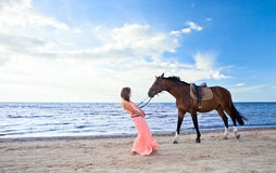 Girl with horse on seacoast Royalty Free Stock Photo
