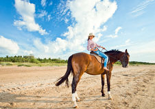 Girl with horse on seacoast Stock Images