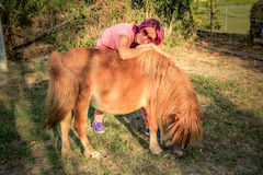 Woman and pony. Young woman hugging a Shetland pony in the countryside Royalty Free Stock Photos