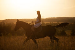 Girl on a horse at sunset Stock Photography