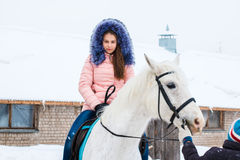 Girl, horse trainer and white horse in a winter Royalty Free Stock Photos