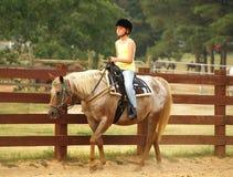 Girl on Horseback. A girl walking a horse along a fence stock image