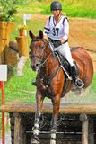 Girl horseback jumping cross country stock photography