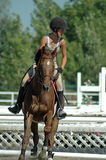 Girl horseback riding. Teen girl riding brown horse in arena during equestrian event Stock Image
