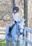 Girl at horseback riding lesson. Royalty Free Stock Photography