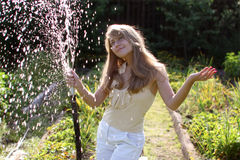 Girl with hose. Beautiful girl in the garden with hose Stock Image