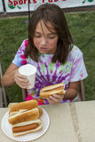 Girl in hot dog eating constest. A girl participates in  a hot dog eating contest during Taste of Rathdrum, Idaho USA Royalty Free Stock Photos