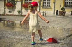 Girl in hot summer city with water sprinkler Stock Image