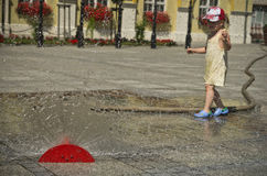 Girl in hot summer city with water sprinkler Royalty Free Stock Image