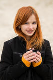 Cheerful smiling red-haired girl with cute smile red hot coffee. Stock Photos