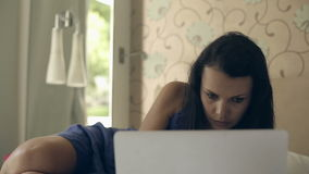 Girl in a hotel room talking on the Internet through your macbook. Video with sound. Medium shot stock video footage