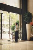 A girl hotel worker meets visitors at the main entrance. stock photo